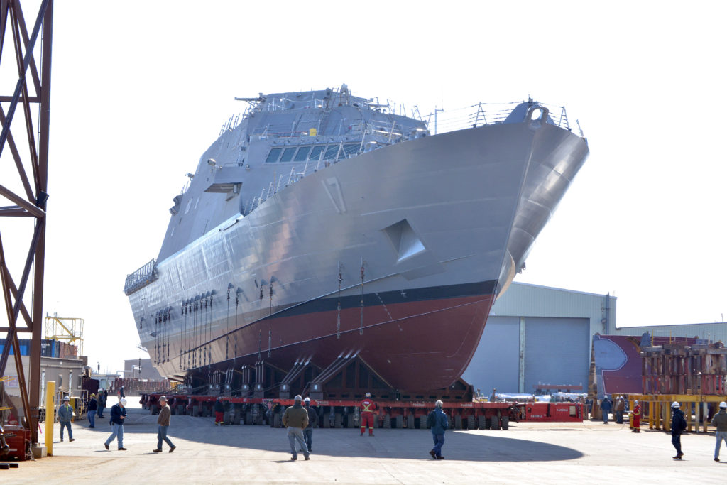 The future littoral combat ship USS Indianapolis (LCS-17) is moved from an indoor production facility in Marinette, Wisconsin, to launchways in preparation for its upcoming launch into the Menomenee River (U.S. Navy photo courtesy of Marinette Marine by Val Ihde/Released)