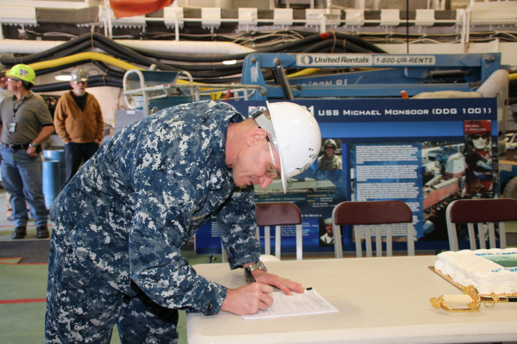 Commander John Bauer, DDG-1000 program manager's representative, signs paperwork accepting delivery of the future USS Michael Monsoor (DDG-1001). Following a crew certification period, Michael Monsoor will transit to its homeport in San Diego, California, for commissioning in January 2019 (Photo by U.S. Navy photo courtesy of Bath Iron Works/Released)