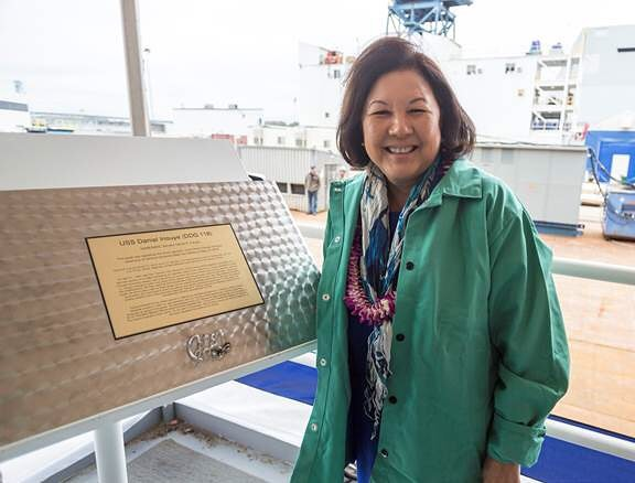 Irene Hirano Inouye, wife of the late senator, is the ship's sponsor. Assisted by Frank Wood, a 31-year Bath Iron Works welder, the sponsor authenticated the laying of the keel by striking welding arcs onto a special steel plate containing her initials