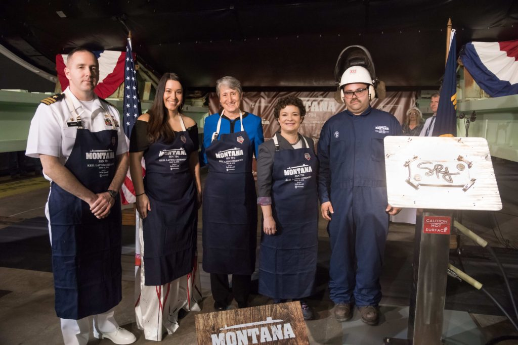 Jacob McNulty (far right) displays the keel authentication plate he welded at today's ceremony. Also present for the ceremony were (left to right) Commander Mike Delaney, commanding officer of the pre-commissioning unit Montana; Mariah Gladstone, a member of the Blackfeet Nation; former Secretary of the Interior Sally Jewell, the ship's sponsor; and Newport News Shipbuilding President Jennifer Boykin (Photo by Matt Hildreth/HII)