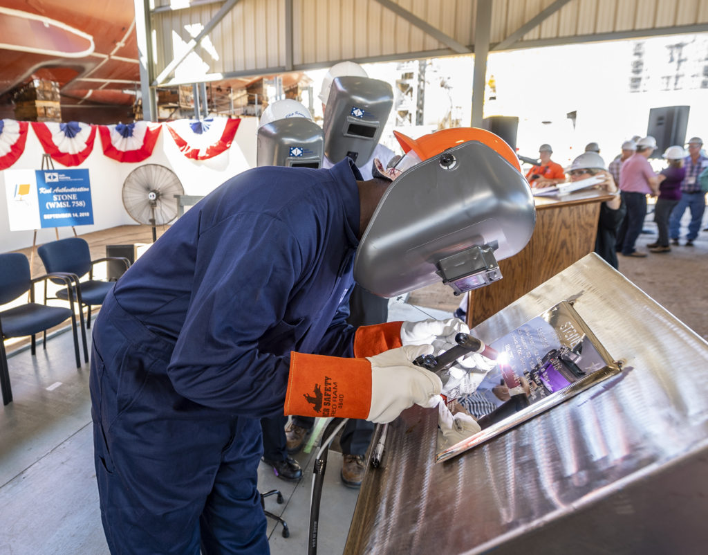 Demetrica Hawkins, a structural welder at Ingalls Shipbuilding, welded ship sponsor Laura Cavallo's initials onto a steel plate, signifying the keel of NSC 9 as being «truly and fairly laid». The plate will remain affixed to the ship throughout its lifetime (Photo by Derek Fountain/HII)