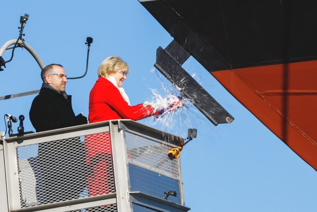 Ship sponsor Barbara Broadhurst Taylor breaks a bottle of sparkling wine across the bow during the christening ceremony for the nation's 19th Littoral Combat Ship, the future USS St. Louis