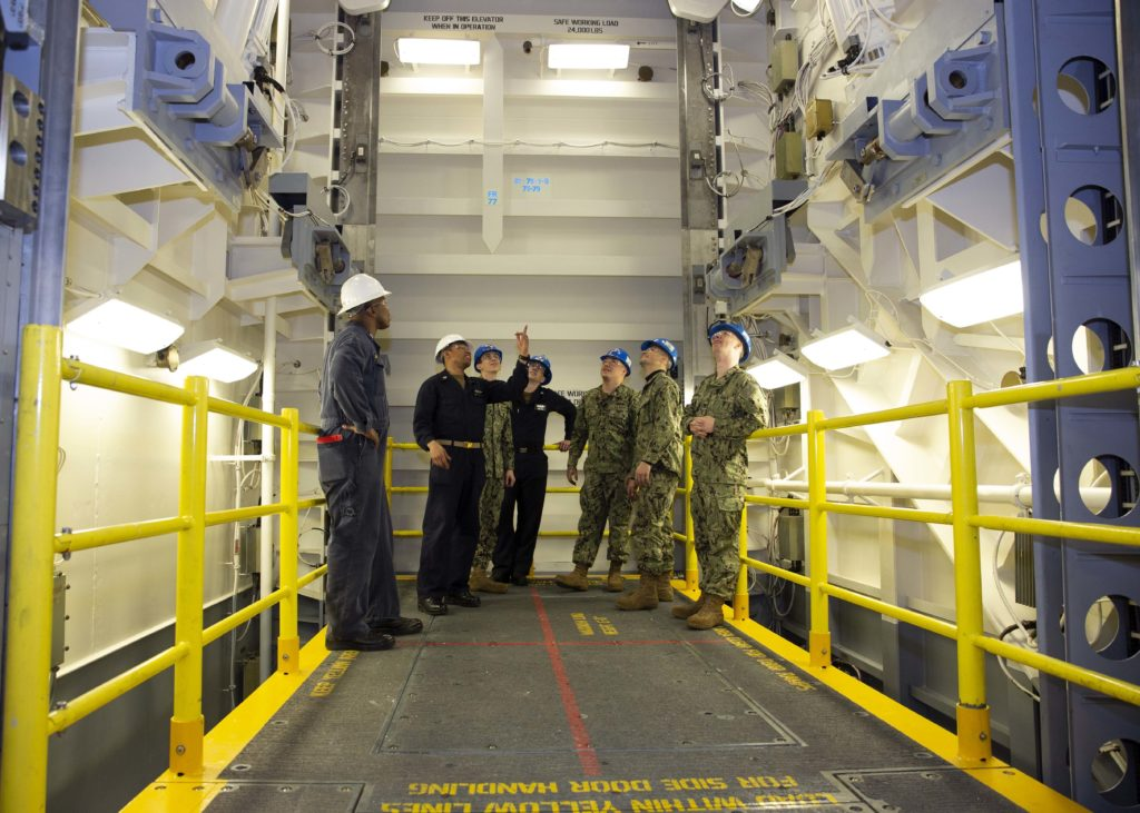 Chief Machinist's Mate Franklin Pollydore, second from left, from Georgetown, Guyana, goes over safety procedures for the Upper Stage 1 advanced weapons elevator with Sailors from USS Gerald R. Ford's (CVN-78) weapons department. The elevator is the first to be delivered to the ship and marks a major milestone for Ford and the entire Ford-class of aircraft carriers. Ford is currently undergoing its post-shakedown availability at Huntington Ingalls Industries-Newport News Shipbuilding (U.S. Navy photo by Mass Communication Specialist 1st Class Jeff Troutman/Released)