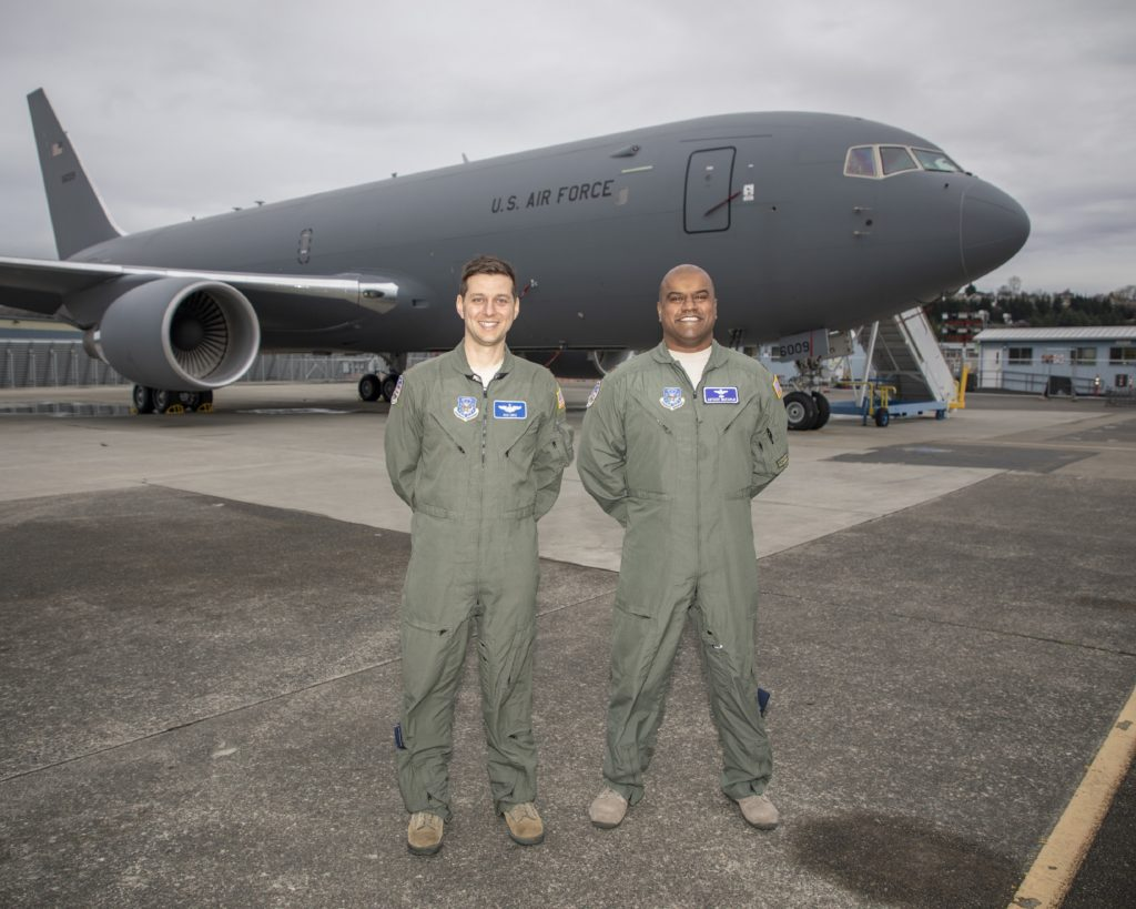 Nick Cenci, Major, USAF Chief of Flight Operations DCMA (Seattle) (left) and Anthony Mariapain, Major, USAF KC-46 Chief Pilot DCMA (Seattle) stand in front of the KC-46A Pegasus at Boeing Field in advance of the U.S. Air Force acceptance of Boeing's first tanker. Major Cenci and Major Mariapain led flight acceptance testing on the jet (Boeing photo)