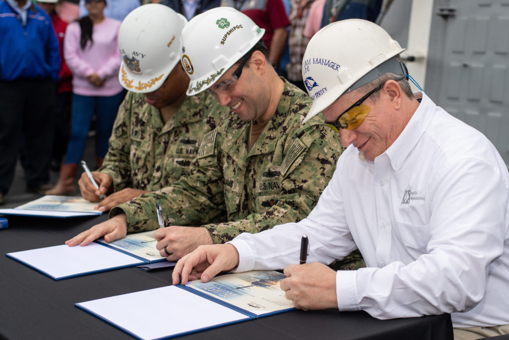 (Left to right) Commander Robby Trotter, Commander Scott Williams and Donny Dorsey sign the delivery document officially handing ownership of the destroyer USS Paul Ignatius (DDG-117) from Ingalls Shipbuilding to the U.S. Navy. Trotter is the ship's prospective commanding officer; Williams is the DDG-51 program management representative for Supervisor of Shipbuilding, Gulf Coast; and Dorsey is Ingalls' DDG-117 ship program manager (Photo by Derek Fountain/HII)