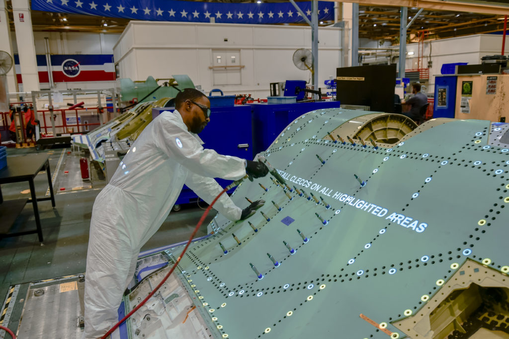An F-35 technician performs a skin assembly process with work instructions projected on the structure as one of the innovative solutions for high rate military aircraft production. A core structure of the F-35 Lightning II aircraft, the center fuselage is produced on Northrop Grumman's integrated assembly line at its Palmdale Aircraft Integration Center of Excellence