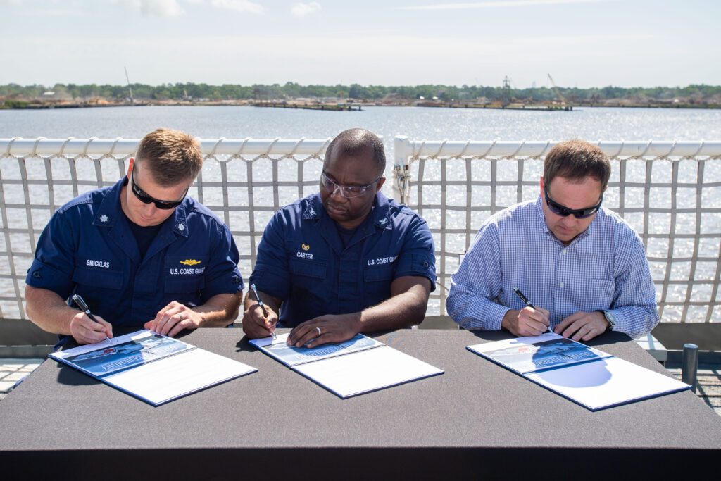 With the signing of the ceremonial documents, custody of the National Security Cutter USCGC Midgett (WMSL-757) is officially transferred to the U.S. Coast Guard. Pictured (left to right): Commander Brian Smicklas, executive officer, USCGC Midgett (WMSL-757); Captain Travis Carter, commanding officer, Project Resident Office Gulf Coast; and Derek Murphy, Ingalls' NSC program manager (Photo by Derek Fountain/HII)